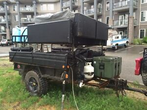 Off road camping trailer with a rooftop tent.