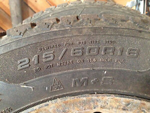4 STUDDED GOODYEAR M+ S TIRES 215/ 60R16 WITH RIMS.