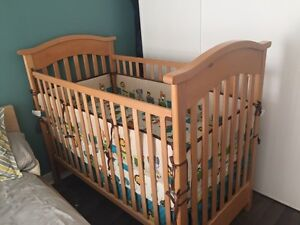 Wooden crib with mattress and bedding