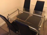 Glass topped dinning table and black chairs