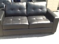 Black leather two seater sofa .