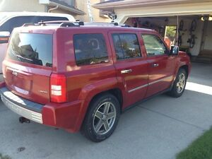 Red 2008 jeep patriot.