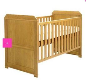 Wooden cot that turns into a toddler bed with mattress.