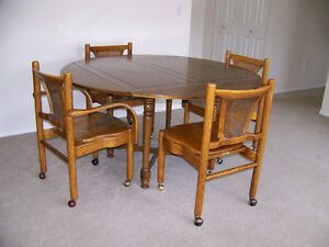 Dining table with 4 solid oak chairs on casters.