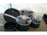 3 s aucepans with lids a frying pan and a milk pan