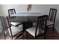 Dark wood oval table 140x100 cm, folds to 30 cm. Upholstered chairs.