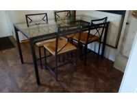 IKEA dining table and 4 chairs. Black metal framework and glass top. Rattan seat chairs