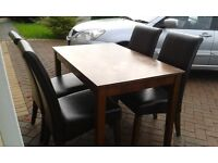 Dining table and 4 chairs, leather chairs 1 has slight rip on seat. Table measures 120 cms in length