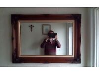 a large wooden frame mirror that is old and in good condition