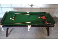 Pool Table with two cues and a full set of both snooker and pool balls.