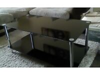 Black glass coffee table and cream long pile rug.