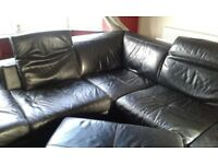 Black leather corner sofa with footstool