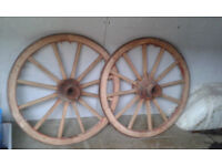 a pair of old wooden wagon / cart wheels
