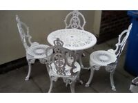 Cast iron table and four chairs in excellent condition..