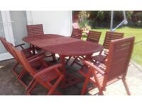 Wooden garden table (extendable) with eight chairs and chair covers.