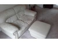 Cream 2 seater leather sofa and matching pouffe.