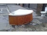 Conner bath tub with wooden panel as seen