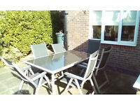 Glass topped garden table with six folding chairs. good condition