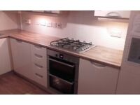 Cream handless kitch and worktop with gad hob, extractor and sink