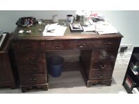 reproduction, wooden, two-pedestal desk with green leather-look top.