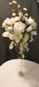 Large faux flowers in elongated clear vase for weddings.