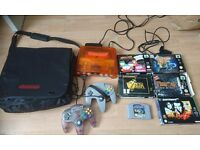 Rare transparent orange Nintendo N64 with games and retro gamebag