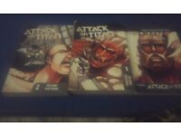 Attack on titan manga volme 1 and 2 with a other manga book