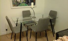 clear glass dining table with 4 chairs.