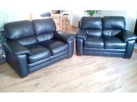 Two 2 seater black leather sofas