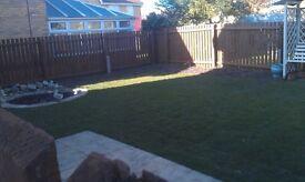 gardener turfing lawn fence decking