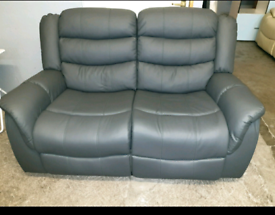 A like new grey leather effect 2 seated reclining sofas.