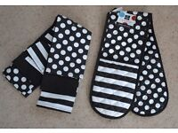 Brand new unused matching set of black and white oven gloves and two tea towels