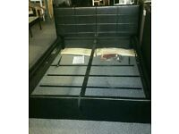 A brand new stylish shiny black leather effect king size ottoman bed frame.