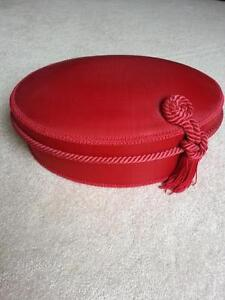 Decorative red oval box with tassle