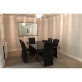 Black extendable dining table with wooden base and 6 black leather chairs