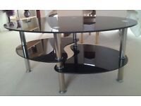 Coffee table black glass oval 2 shelves underneath.