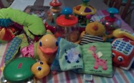 Ten different baby toys including spinning tops, pull - a-long phone, ducks, long snake etc.