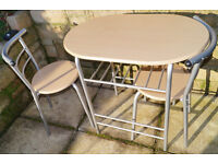 A compact breakfast table and two chairs