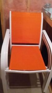 4 bright orange and white stackable lawn chairs