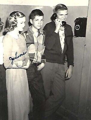 c1950 cute blonde teen boys & glamorous teen girl wait in line to use wall phone