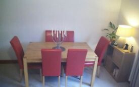 Imaculate condition oak veneer dining table and six chairs in red.