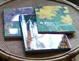 Three different gardening books.One is called The Plant guide, one annuals,one a garden year.