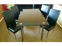 Black glass table and four pvc chairs