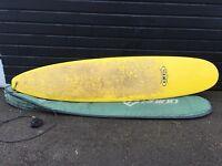 8 foot yellow Tiki surfboard with board bag.