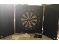 Darts board in wooden enclosure with 2 packs of vintage darts