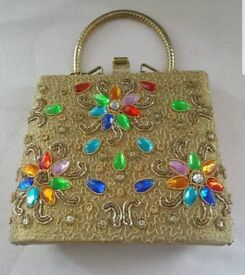 ladies gold colour handbag with different colour studs on it