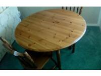 Pine drop leaf circular dining table and two dining chairs for sale