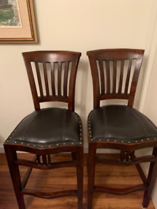 Two wooden bar stools with leather seats