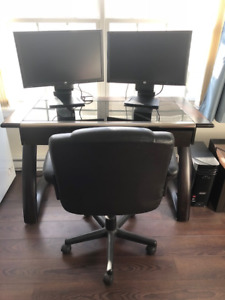 Computer desktop complete with monitors, cabling, desk, chair