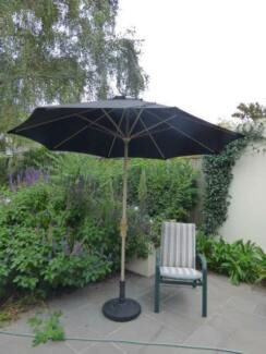 Large black outdoor umbrella and stand